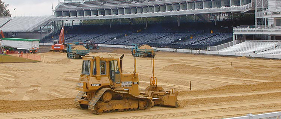 Diggers creating a pitch surface in a stadium